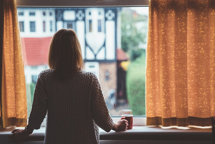 Woman at home looking out a window.
